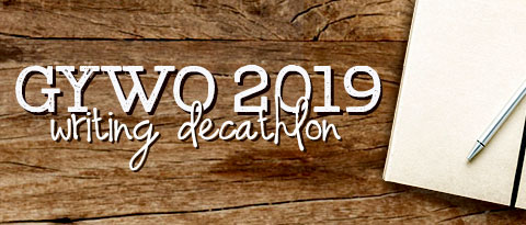 notebook and pen on wooden desktop with 'GYWO 2019' printed in large white letters with a black shadow. under that, 'writing decathlon' in handwritten white letters with a black shadow.